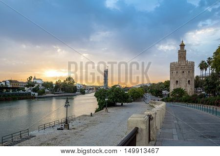 Golden Tower with cityscape and river of Sevilla sunset Seville, Spain