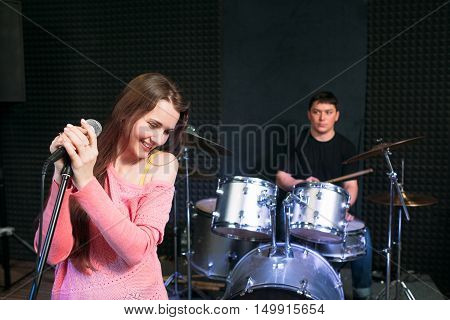 Shy female singer near microphone on scene, drummer on background. Young attractive woman confusedly smiling on performance