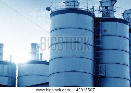 Cement silo under backlit blue tone image.
