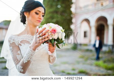Stylish Brunette Bride With Bouquet At Hand
