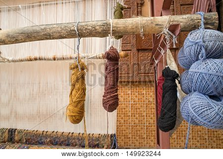 Bundles of naturally dyed yarn on a wooden loom next to a wall with Indian wooden carvings. Craftsmanship and local industry concept.