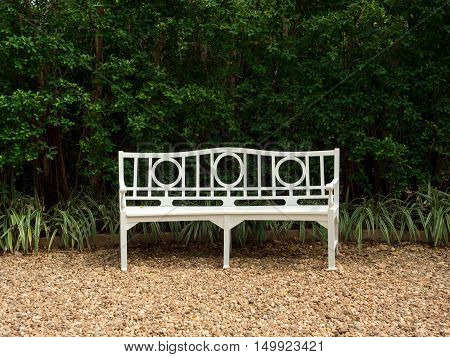 Elegant white park bench in front of a tall hedge and pebble floor. Relaxation and simplicity background concept.
