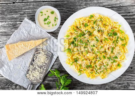 Fettuccine Alfredo served in a sauce of cream butter and grated Parmesan cheese sprinkled with parsley. piece of parmesan cheese on parchment paper on old planks view from above