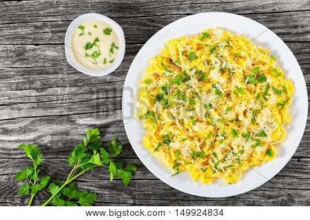 Fettuccine Alfredo served in a sauce of cream butter and grated Parmesan cheese sprinkled with parsley on white dish on old planks view from above