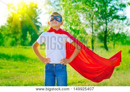 Super Hero Kid having fun outdoor. Superhero little boy over nature green blurred background