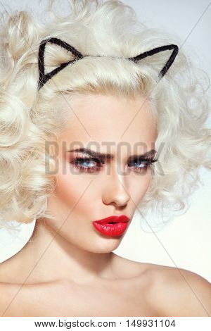 Close-up portrait of young beautiful platinum blonde sexy woman with fancy hairdo and cat ears headband