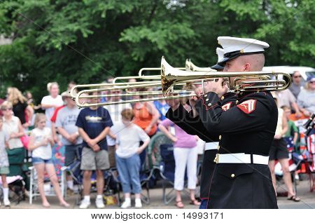 The Usmc Marine Forces Reserve Band Performers Playing Trombones In A Parade