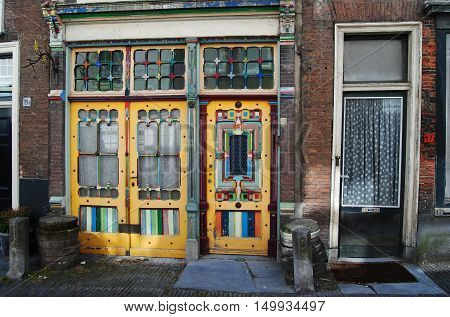 Leiden, The Netherlands - May 13, 2014. Multi-color door of a residential house in Leiden, with adjacent door and brick wall.