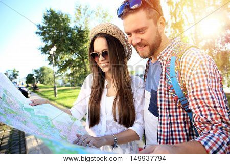 Happy couple walking outdoors sightseeing and holding a map