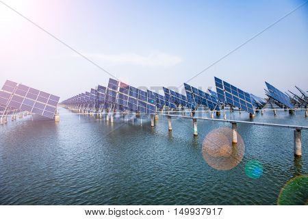 group of solar panels over river against blue sky,china.