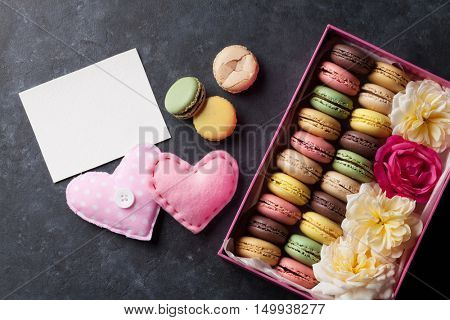Colorful macaroons and greeting card. Sweet macarons in gift box and hearts. Top view with copy space for your text