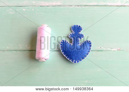 Blue felt anchor, white thread, needle on wooden background. Two pieces of felt in the shape of an anchor stitched with white thread. Basic sewing crafts for kids. Tutorial. Step