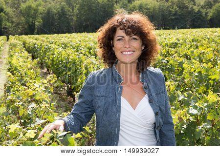 Happy woman winery owner posing in the vineyard
