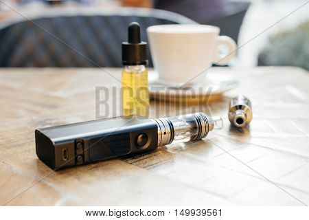 Vaping. Vaporizer or electronic cigarette on the table