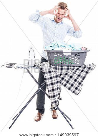 Young man completely overwhelmed with his laundry and the electric iron - isolated on white background