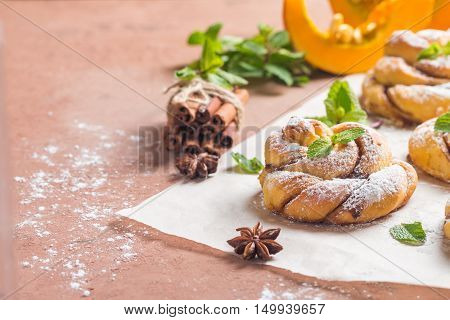 Homemade cinnamon buns with pumpkin on paper over brown background,