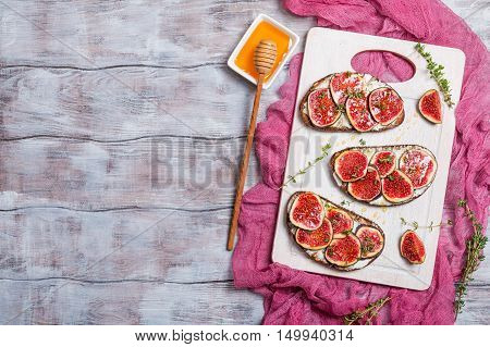 Fresh bread with figs, ricotta and honey on white cutting board, top view with copy space