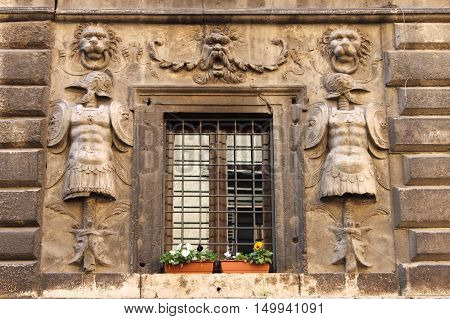 Renaissance window with flower pots and grate in Rome, Italy