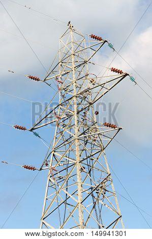 High voltage electricity pylon against a cloudy sky