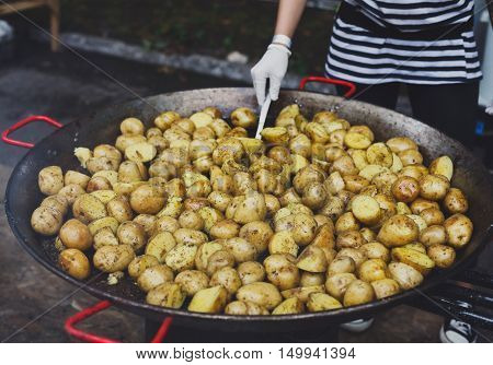 Country fair, vendor cooking. Roasted potatoes cooked outdoors in big metal cauldron pot. Cookout vegetable meals. Fresh organic snack, potatoes cooked on grill flame. Street food, fast food.