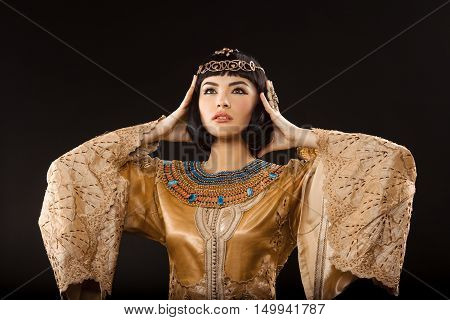 Woman having headache. Glamorous closeup portrait of beautiful sexy stylish brunette young woman model with bright makeup. Cleopatra