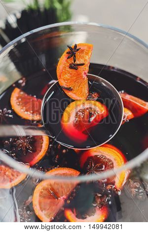 Making hot alcohol, mulled wine for sale at country fair. Glintwine from red wine with citrus and cloves in big glass, mixed with soup ladle. Closeup, vertical image