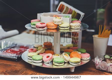 Beautiful Macarons choice. Plenty of colorful french cookies, meringue based confectionery desserts on counter bar for sale. Pastel colors, packed in boxes and stacks closeup