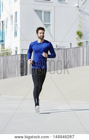 Man jogging in sports clothing in town