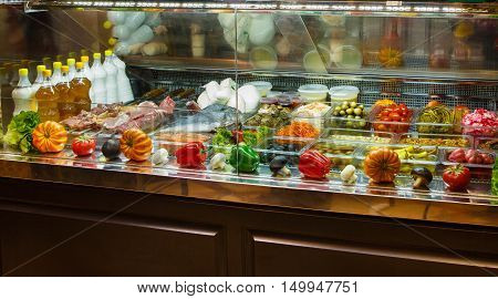 Variety of meat, fish, pickled vegetables and mushrooms in a store. Glass showcase in grocery store with food for picnic and home.