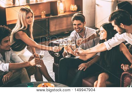 Cheers to best friends ever! Top view of cheerful young people enjoying food and drinks while spending nice time in cofortable chairs on the kitchen together