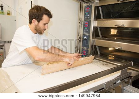 Male Baker Baking Fresh Bread In The Bakehouse Near Oven