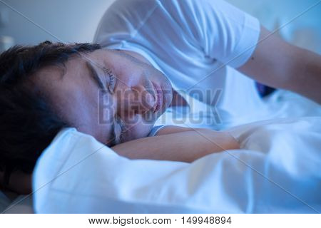 Man lying in the bed and sleeping at night