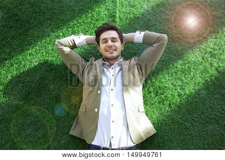High angle view of relaxed young businessman lying on turf