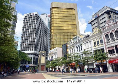 Kuala Lumpur, Malaysia - November 29, 2015. City square in downtown Kuala Lumpur, with clock tower, commercial and residential buildings and people.