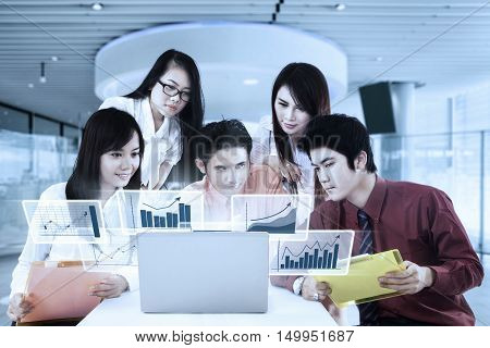 Portrait of Asian business team in a business meeting with virtual financial chart on the laptop