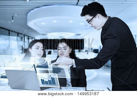 Three business people discussing in the office with virtual graph and laptop computer
