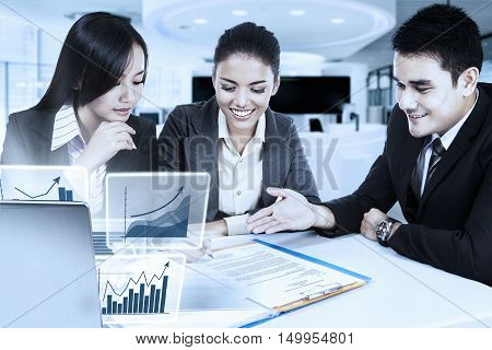 Young businesswoman signing a business contract with her partners and virtual financial graph on the laptop