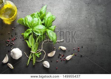 Basil leaves garlic pepper at dark slate background. Space for text. Ingredients for cooking.