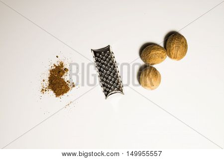 Nutmeg nut and powder in a white background