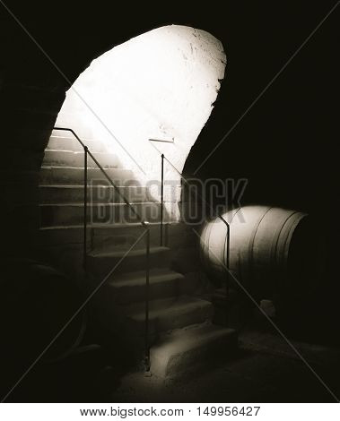 Aged stone stairs and bright light - Vintage image with old stone stairs going into an antique cellar with a strong beam of light coming down.