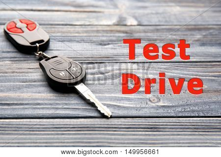 Test drive concept. Car key on wooden table