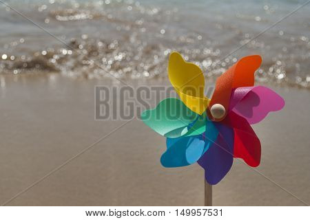 Rotating colorful rainbow pinwheel on the beach, closeup