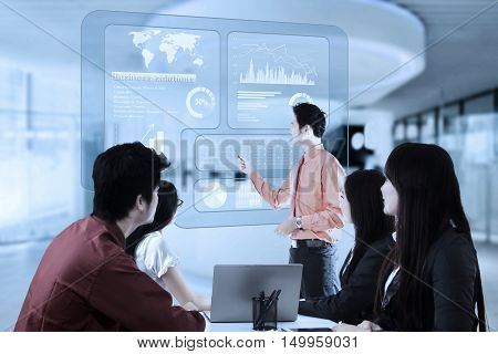 Young businessman presentation with virtual financial statistics and his partners in the office