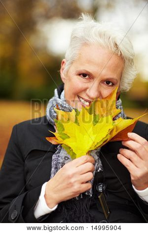 Senior Woman With Maple Leaves