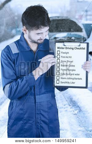 Young mechanic wearing blue uniform and holding clipboard with winter driving tips