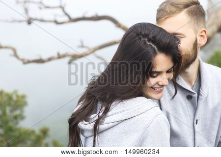 Young loving couple relaxing and hugging she is smiling and leaning on his shoulder relationships and feelings concept