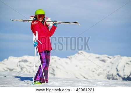 Girl standing with ski on the arms on the fresh powder snow at sunny day in mountains. Swiss Alps.