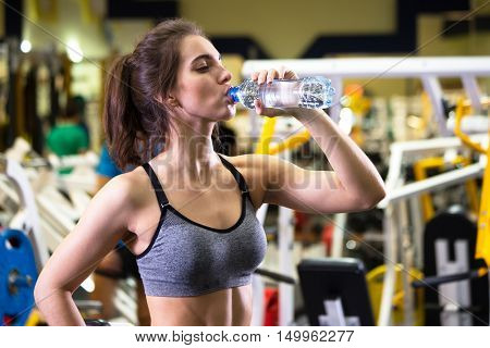 Fitness woman drinking water from bottle. Young female at gym taking a break from workout.