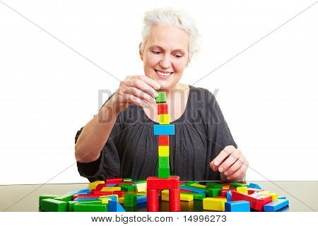 Senior Woman Building With Colorful Bricks