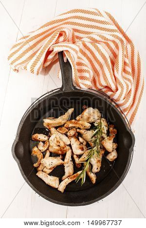 cut into small pieces turkey breast with crushed black peppercorn and rosemary in a cast iron pan